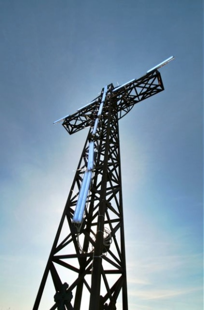 Blue neon lights attached to the cross at the top of Monte Acuto