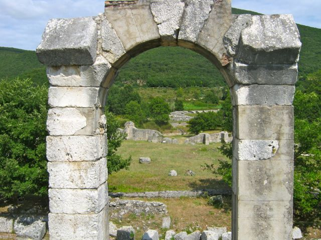 An arch and some of the runs of Carsulae, a ruined Roman town